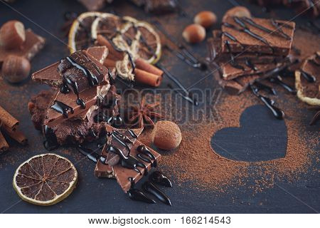 Chocolates background. Lemon nuts cookies and assortment of fine chocolates in dark and milk chocolate on dark background.