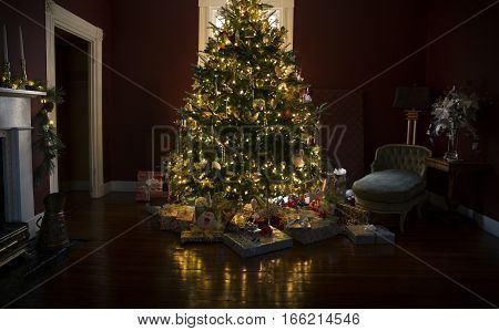 Christmas tree with presents and lights reflected on the wooden floor
