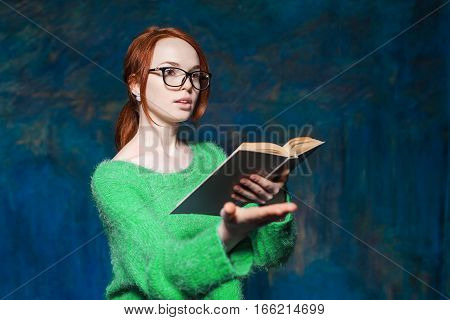 beautiful red-haired teacher in green sweater and glasses reading book and gestures over magic dark blue background