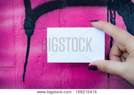 Female hand holding blank white business card over colorful background.