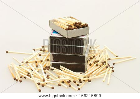 Matches in boxes and scattered matches on a light background