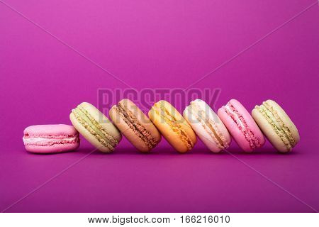 Row Of Sweet Colorful French Macaroon Biscuits On Purple Background