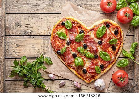 Pizza heart shaped love concept Valentine's Day symbol homemade romantic dinner food. Prosciutto, olives, tomatoes, parsley, garlic, basil and mozzarella cheese baked meal on vintage wooden table