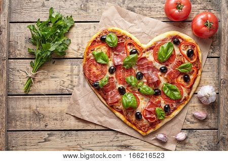 Pizza heart shaped love concept Valentine's Day symbol homemade romantic dinner Italian food. Prosciutto, olives, tomatoes, parsley, basil and mozzarella cheese baked meal on vintage wooden table