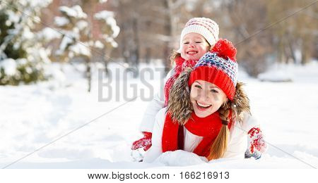happy family mother and child daughter playing and hugging on a winter walk