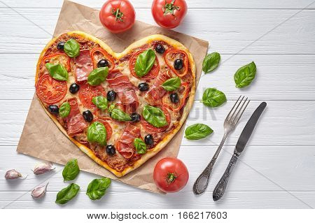 Heart shaped prosciutto pizza hot love concept Valentine's Day design symbol romantic restaurant dinner Italian food. Olives, tomatoes, basil and mozzarella cheese meal served on white background
