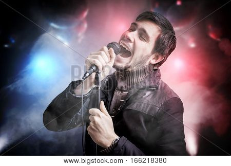 Happy Young Man Is Singing Song In Disco Club At Night.