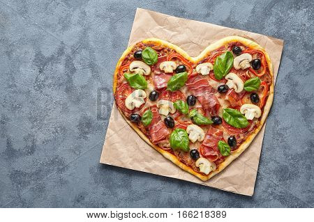 Heart shaped pizza love concept Valentine's Day romantic homemade dinner Italian food. Olives, prosciutto, champignons, tomatoes and mozzarella meal on blue table background. Flat lay.