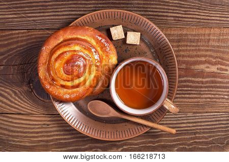 Cup of tea and bun with marmalade in plate on brown wooden table top view