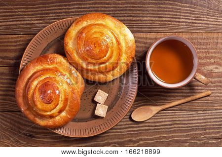 Cup of tea and sweet buns in plate for breakfast on wooden table top view
