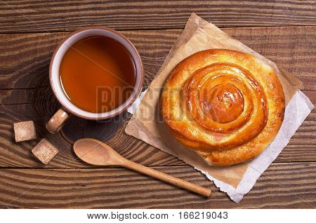 Cup of tea and sweet bun on old wooden table top view