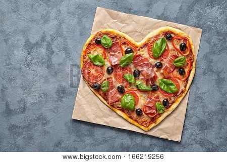 Heart shaped pizza delicious love concept Valentine's Day flat lay design romantic symbol restaurant dinner Italian food. Olives, prosciutto, tomatoes and mozzarella meal on blue table background.