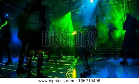 People dancing on defocused blur dance floor background of a disco club with violet, blue and pink strobe lights. Entertainment, leisure and nightlife concept. Adult lifestyle.