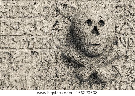 Skull and bones at an antique and weathered tombstone