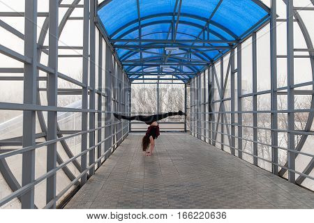 Beautiful young sports woman doing stretching outdoors in transition. The girl is engaged in fitness outdoors.