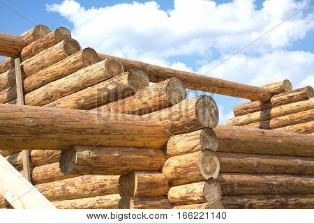 Top of blockhouse. Construction of rural house from logs on a background of blue sky with clouds