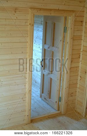 Opened door inside new built wooden house vertical view