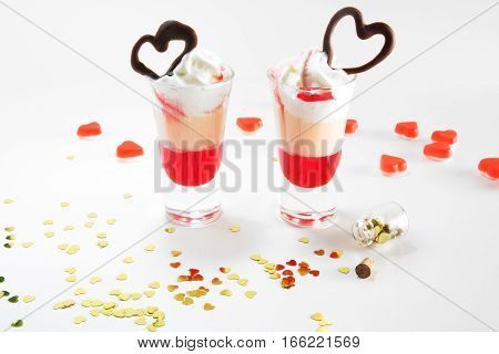 Multi-layered cocktail shot, close-up. Short cocktail with milk, syrup, cream, decorated with heart made of chocolate. Saint valentine's day.