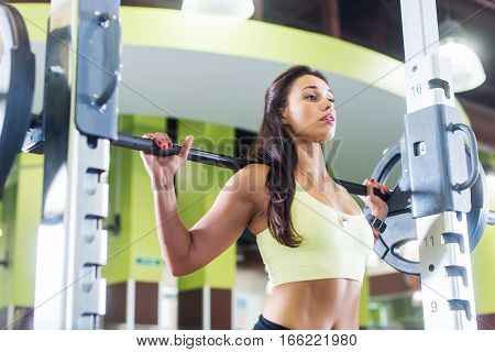 Fit woman doing squats with a barbell in Smith machine