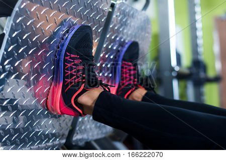 Close up shoes of a fit young woman doing leg press in the gym.