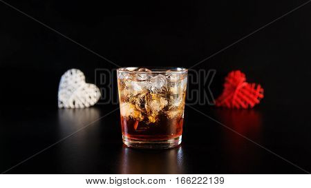 Hearts and a glass of alcohol on a black table in the bar. Lonely scottish glass of whiskey with ice on Valentine's Day.