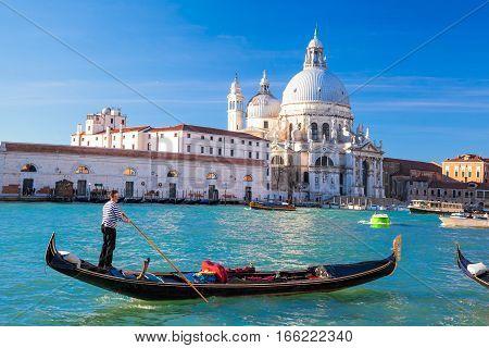 Grand Canal With Gondola Against Basilica Santa Maria Della Salute In Venice, Italy