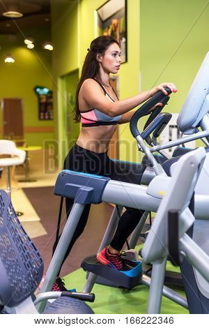 Fit woman exercising at fitness gym aerobics elliptical walker trainer workout
