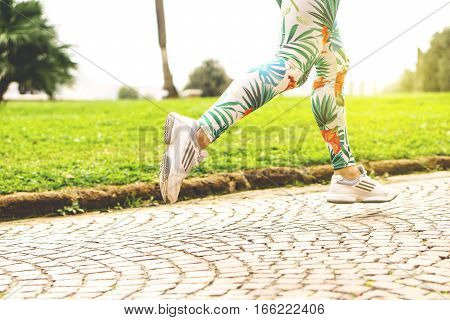 Female legs caught in motion on a concrete trial in a beautiful park - Sportswoman jogging in the nature during the morning - Outdoor activity