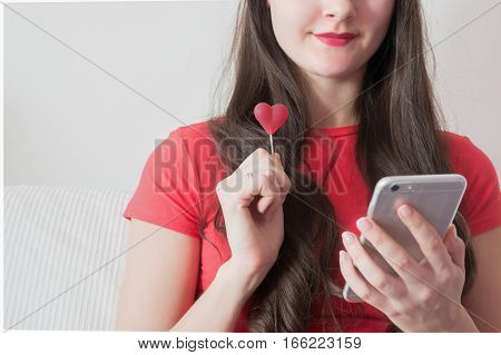 Girl texting on smart phone with red heart shape candy in Valentine's Day