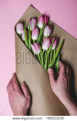 Man's hands wraps pink tulips on craft paper