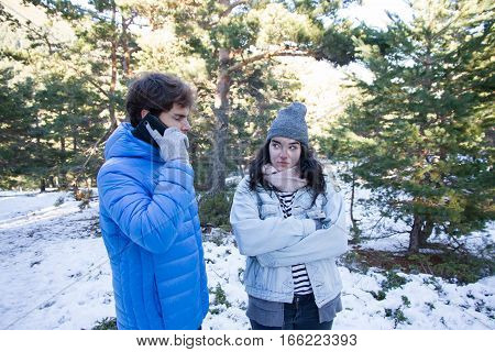 Handsome caucasian guy talking on the phone as he passes from his girlfriend when they are on a date in the snow. It's a trip on a mountain holiday.