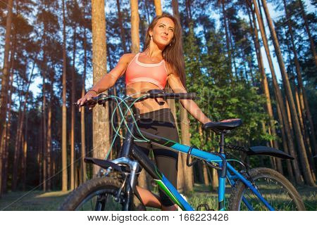 Fit woman with a bicycle in the forest