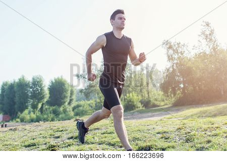 Fit man running outdoor in nature on beach Morning training