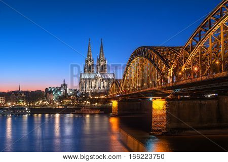 Cologne Cathedral and Hohenzollern Bridge at nighttime. The Cathedral, built in Gothic style in honor of St. Peter the Apostle and the Virgin Mary.