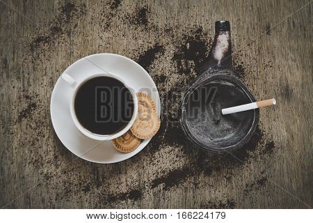 beautiful coffee with rosetta latte art on top of the vintage wooden table and green ashtray: top view shot