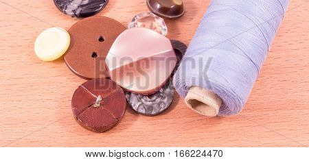 spool of thread and a variety of buttons on a wooden background