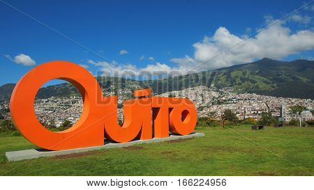 Quito, Pichincha / Ecuador - January 22 2016: Word QUITO made with orange letters in 3 dimensions with the city of Quito in background