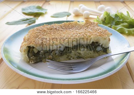 Portion of casserole with potatoes and spinach on a wooden background.