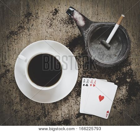 game abstract: coffee cup, ashtray with cigarette and four aces playing cards on the wooden background