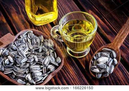 Sunflower oil and sunflower seeds on a wooden table.