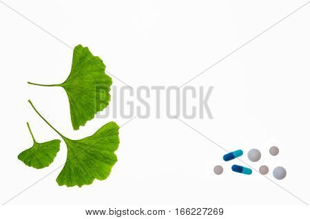 gingko leaves with various pills isolated on white background