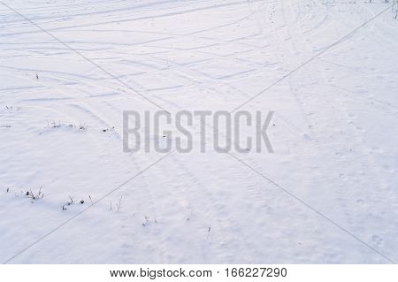snow covered crossroads with tire tracks in perspective view
