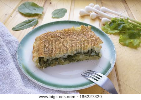 Potato casserole with spinach on a plate and cutlery on a wooden background.