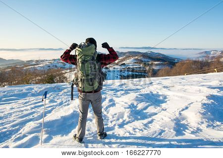 Backpacker Hiking On Snow Covered Mountain