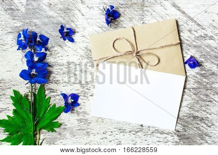Blank white greeting card and envelope with blue wildflowers on white rustic wood background for creative work design. flat lay