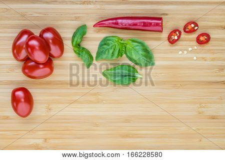 cherry tomatoes, basil leaves and red chilli pepper on wooden board