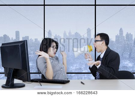 Image of male manager is screaming at his secretary through megaphone while working in the office with winter background on the window