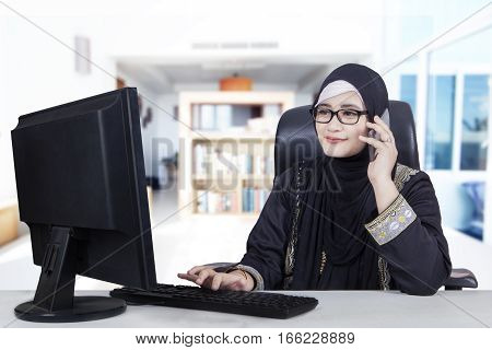 Arabic young woman working at home while wearing islamic clothes and using a computer