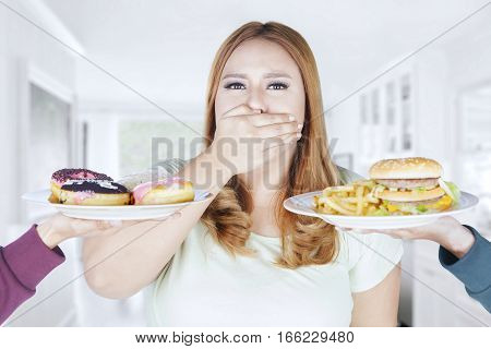 Portrait of beautiful woman refusing high calorie food while closed her mouth with hand