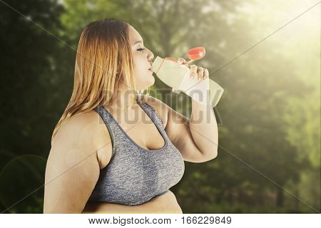 Blonde woman with overweight body drink a bottle of fresh water after workout on the park